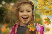 Little girl in autumn with falling leaves and hair in wind — Stock Photo