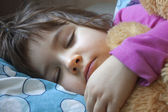 Sleeping child in her bed with teddy bear — Stock Photo
