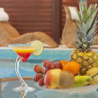 Pool and deck chairs with exotic fruits and drink - Stock Photo