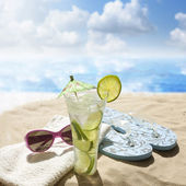 Sunglasses drink in sand on beach at sea holiday concept — Stok fotoğraf