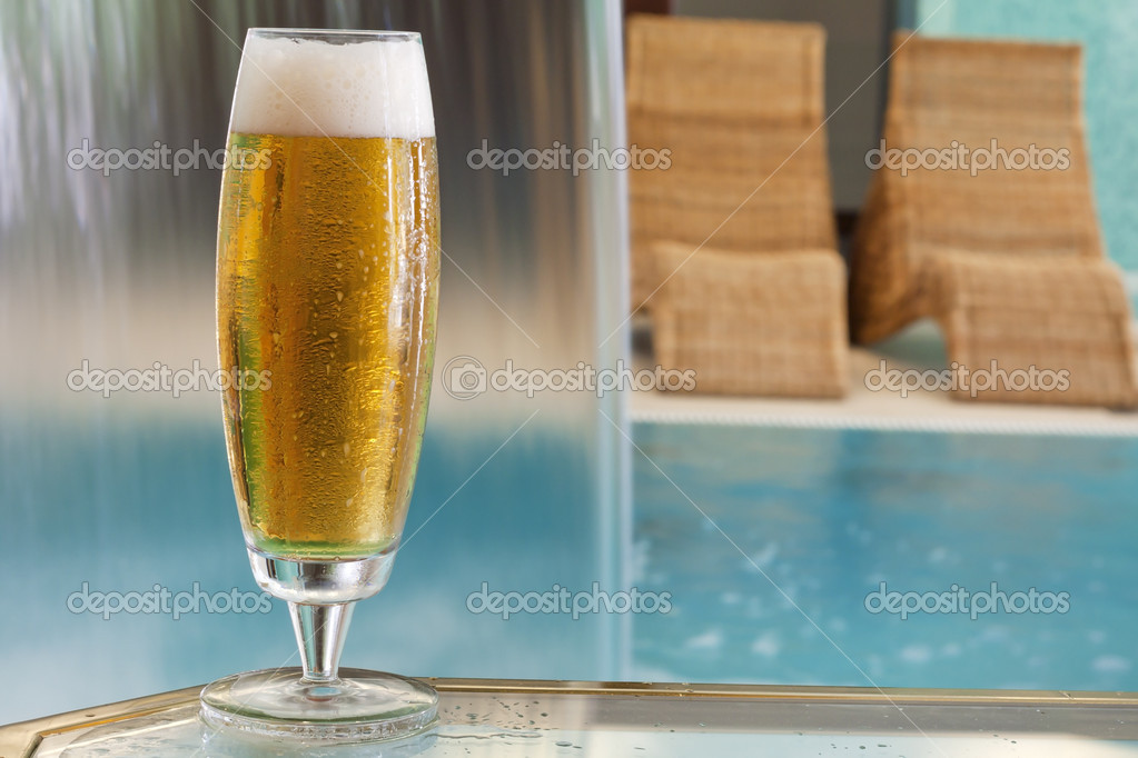 	glass of beer with falling water at pool  Stock Photo #11501966