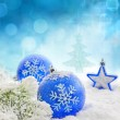 Christmas branch of tree blue baubles and snow background — Stock Photo
