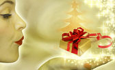 Christmas concept with woman blowing to gift — Stock Photo