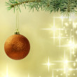Royalty-Free Stock Photo: Christmas red bauble on green tree on golden background