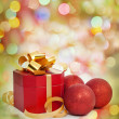 Christmas red gift and baubles on colorful background — Stock Photo