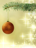 Christmas red bauble on green tree on golden background — Stock Photo
