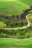 The road in the green hills and stone cliffs — Stock Photo