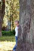 Child hid behind a tree in summer park — Stock Photo
