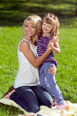 Beautiful young mother hugs her daughter — Stock Photo