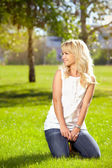 Beautiful girl sitting on the grass in the park — Stock Photo