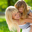 Beautiful young mother holds her little happy daughter on a back — Stock Photo #11342360