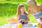 Happy mother and little daughter at a picnic — Stock Photo