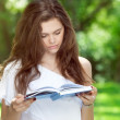 Beautiful young girl reads a book in the park — Stock Photo