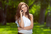 Young beautiful girl talking on the phone outdoors — Stock Photo