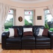 Black couch i front of the window — Stock Photo