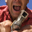 Handyman hammers finger - Stock Photo