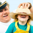Man putting hat on his daughter's head while she laughing — Stock Photo