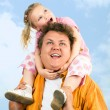 Girl sitting on the daddy's neck - Stock Photo