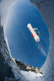 View from below of agile snowboarder in high jump over blue sky — Stock Photo