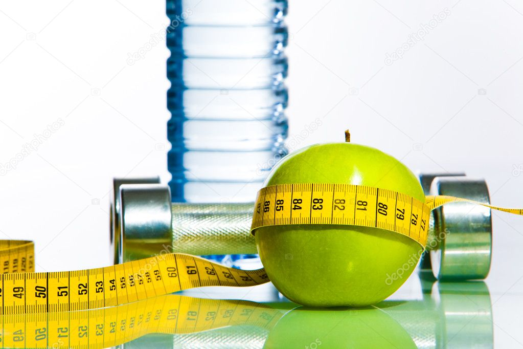 Green apple bounded with measuring tape with two dumbbells and bottle of water behind  Stock Photo #11024217