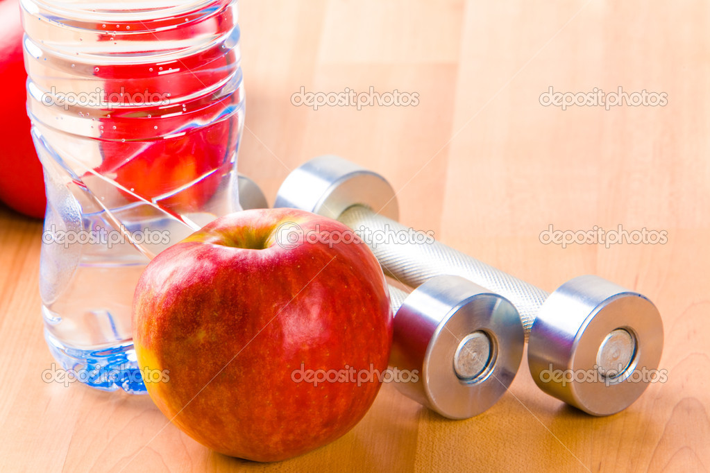 Photo of big red apple with two barbells and bottle of water near by on wooden surface — Stock Photo #11024223