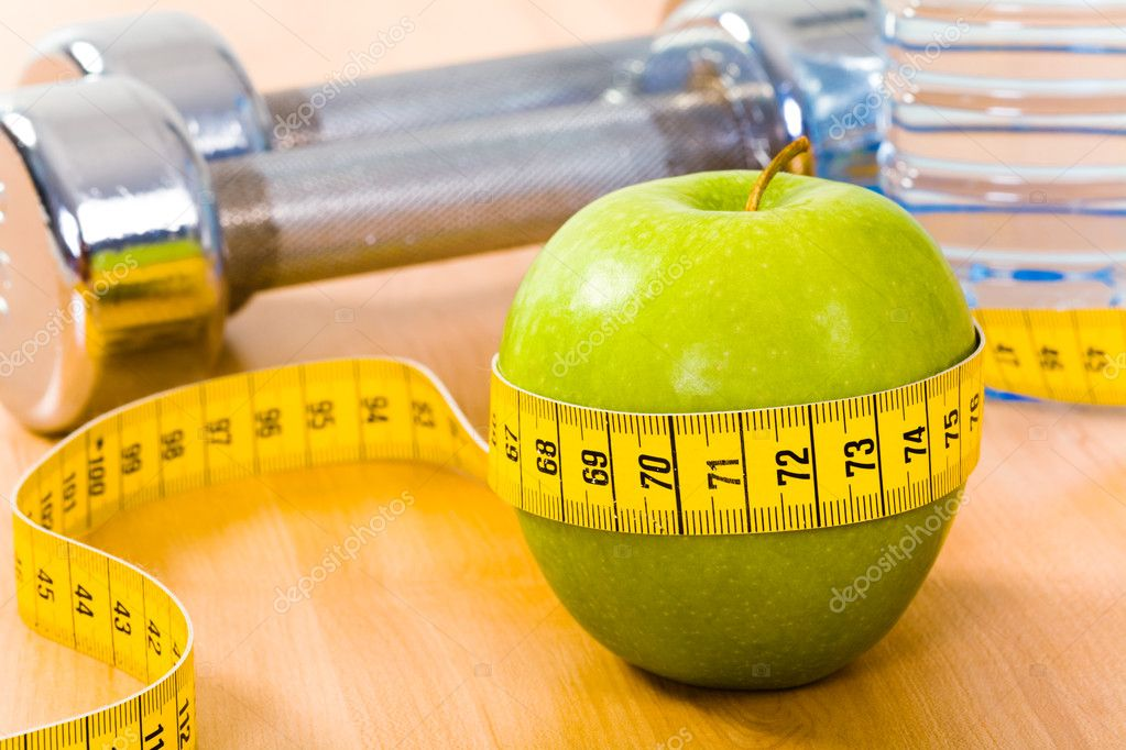 Photo of fresh green apple tied with measuring tape on the background of barbells — Stock Photo #11024288