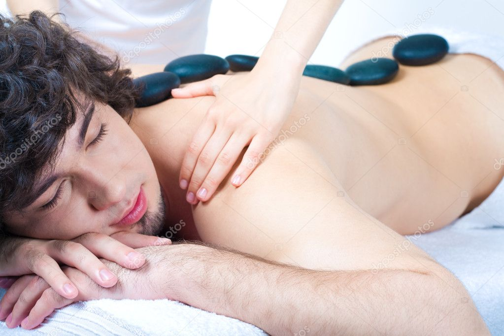 Image of man with spa stone on his back in the salon — Stock Photo #11024539