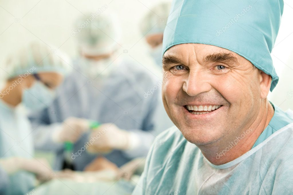 Portrait of senior doctor smiling on the background of his colleagues — Stock Photo #11024923