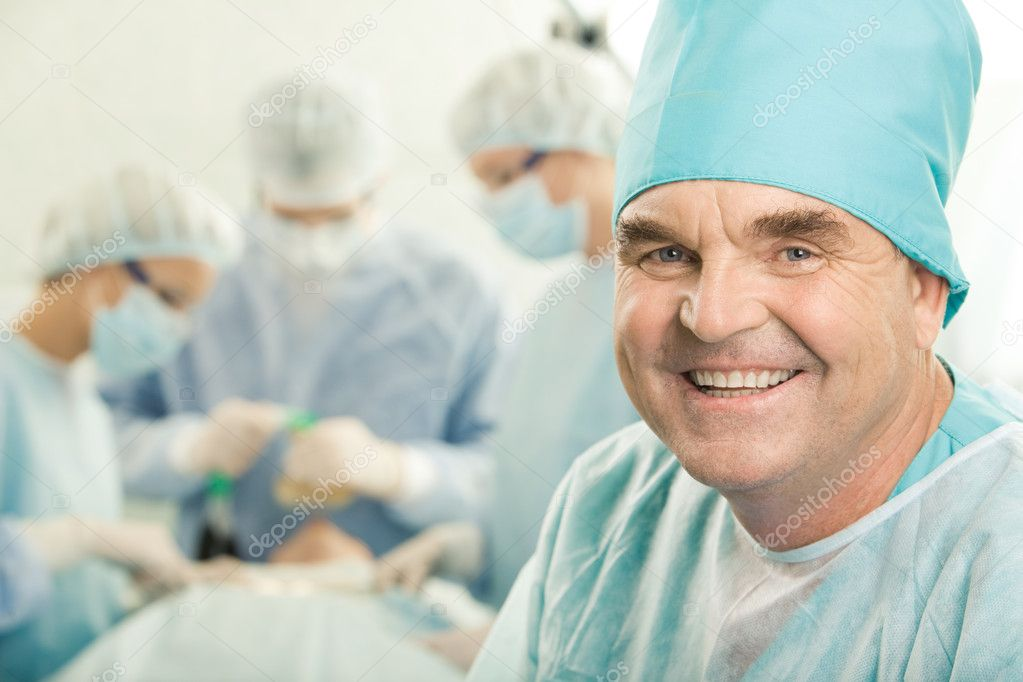 Portrait of happy doctor on background of working surgeons — Stock Photo #11024924