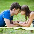 Happy womand her boyfriend resting on green lawn in park — Stok Fotoğraf #11107557