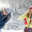 Woman flinging the snowball into her boyfriend — Stock fotografie