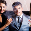 Portrait of successful man smoking a cigar holding whisky with pretty women near by — Stock Photo