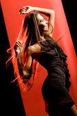 Retrato da bela dançarina usando vestido preto elegante e se movendo sobre fundo vermelho — Foto Stock
