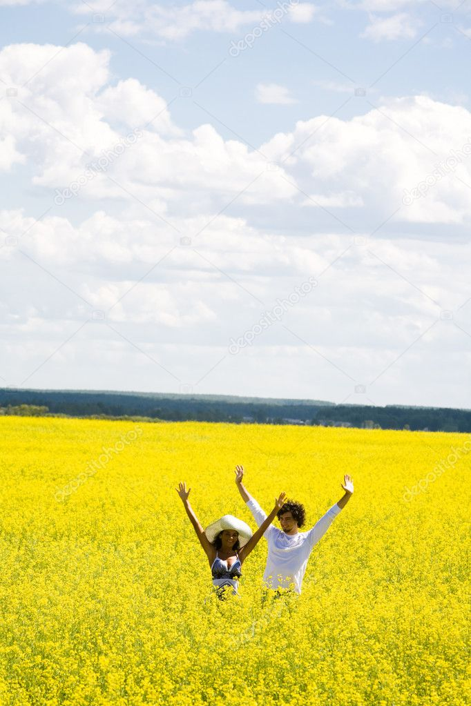 Photo of joyful couple raising their hands while standing in flowery meadow at summer — Stock Photo #11107572
