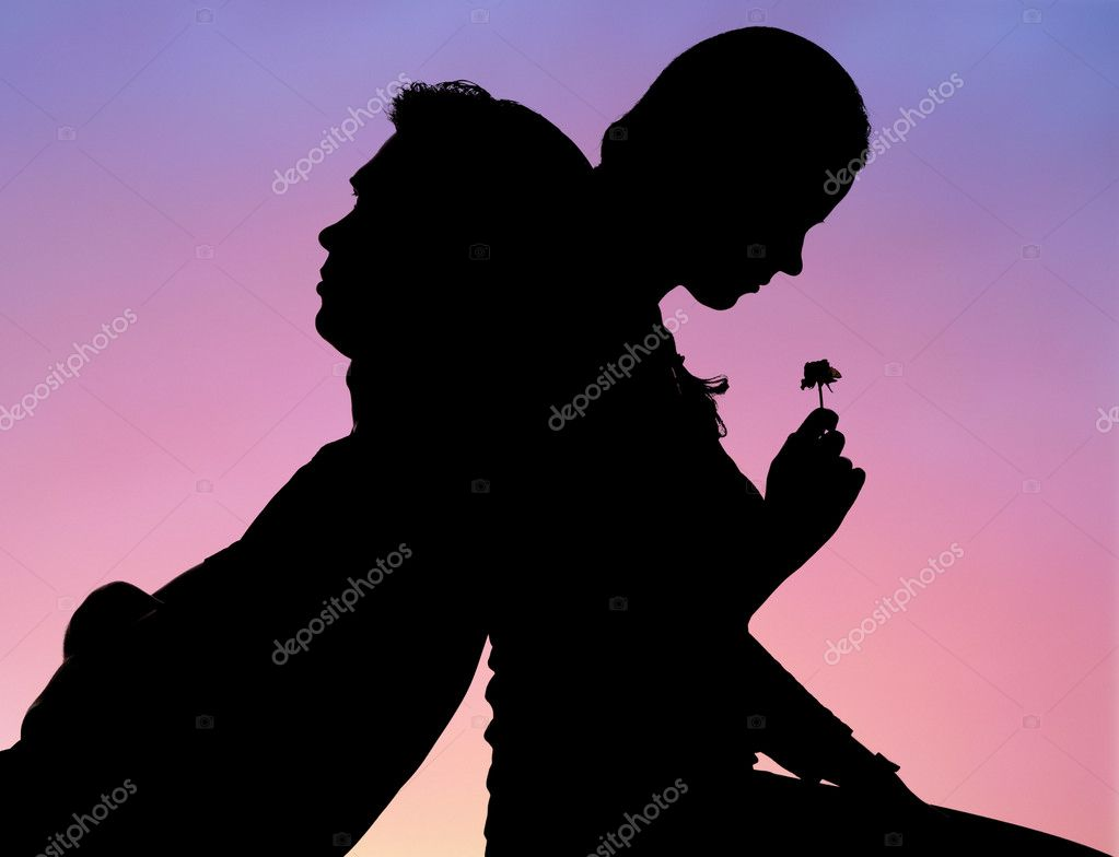 Silhouette of romantic couple sitting back to back on background of sunset — Stock fotografie #11107729