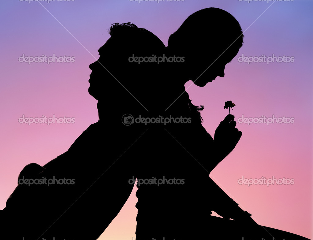 Silhouette of romantic couple sitting back to back on background of sunset  Foto Stock #11107729