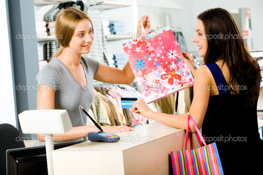 Portrait of shop assistant giving shopping bag to happy woman in the shopping mall — Stock Photo #11107917