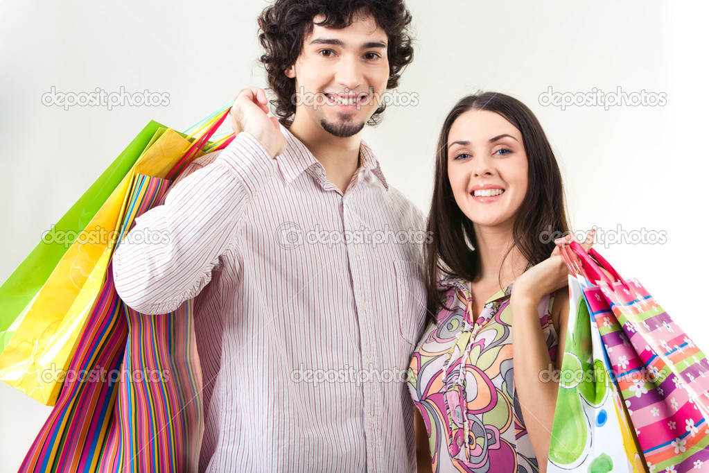 Portrait of young holding bags and looking at camera — Stock Photo #11108104