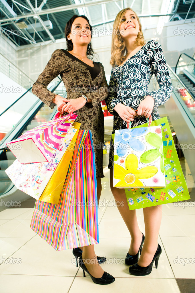 Portrait of two friends with shopping bags in hands standing in the centre — Stock Photo #11108124