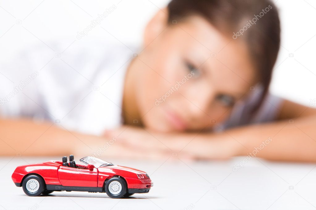 Red toy car on background of woman looking at it — Stock Photo #11108487