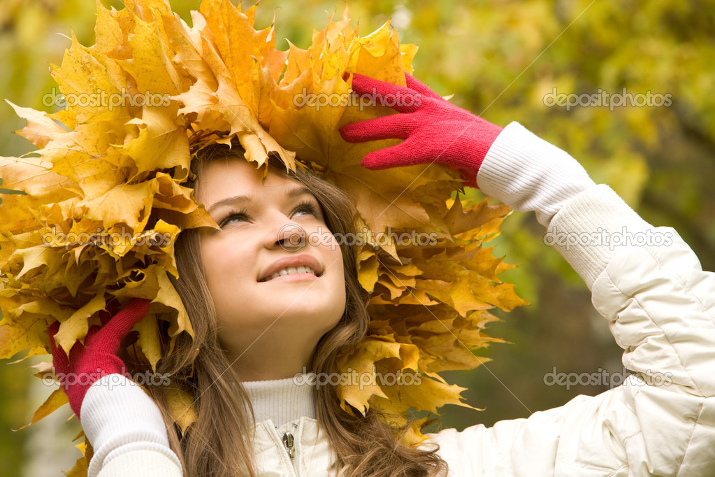 Portrait of smiling young woman touching wreath of maple leaves — Stock Photo #11109049