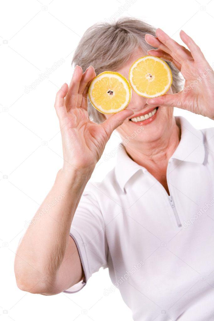 Portrait of mature woman smiling with lemon slices in front of her  Stock Photo #11121347