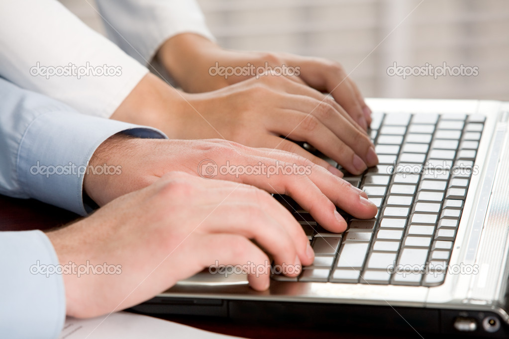 Close-up of two pairs of human hands touching laptop keys  Stock Photo #11121934