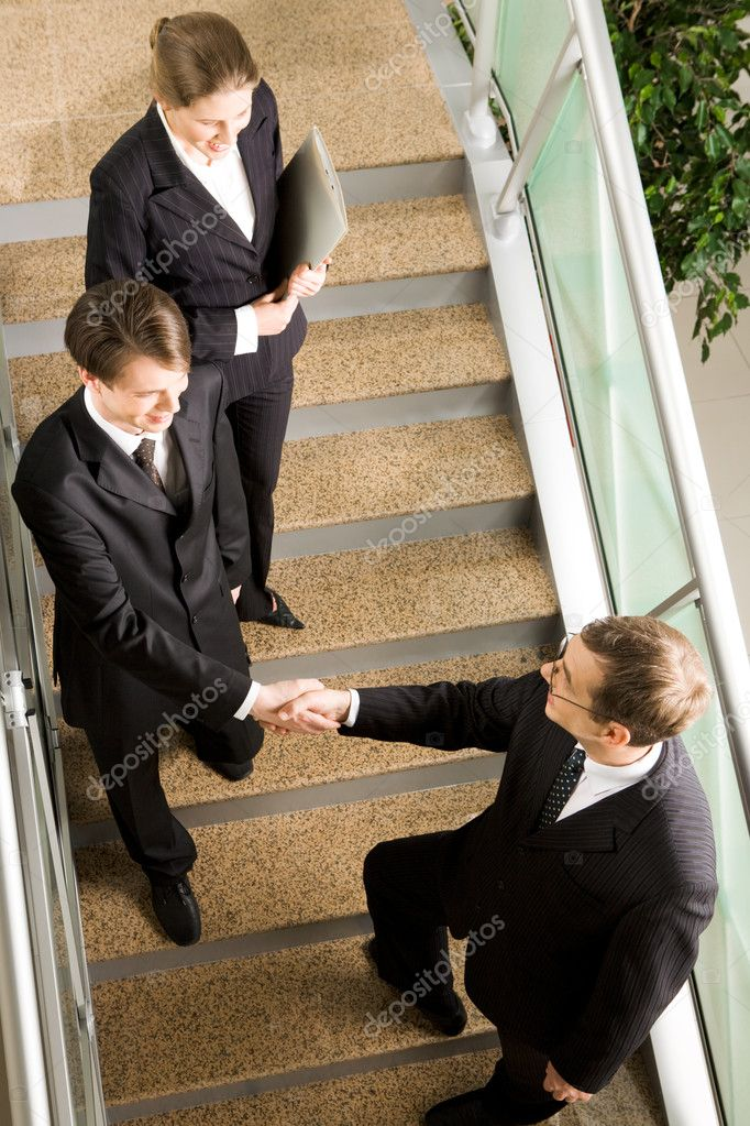 View of handshake of business partners met on the stairs in the office building — Stock Photo #11121973