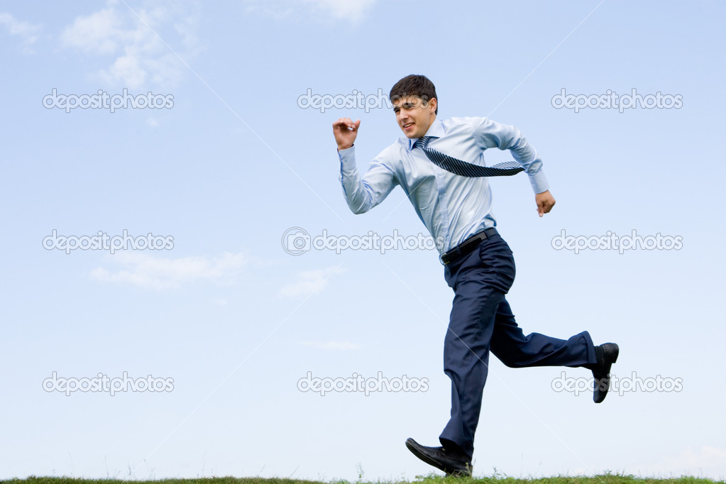 Handsome businessman running down grass with blue sky at background  Stock Photo #11125884