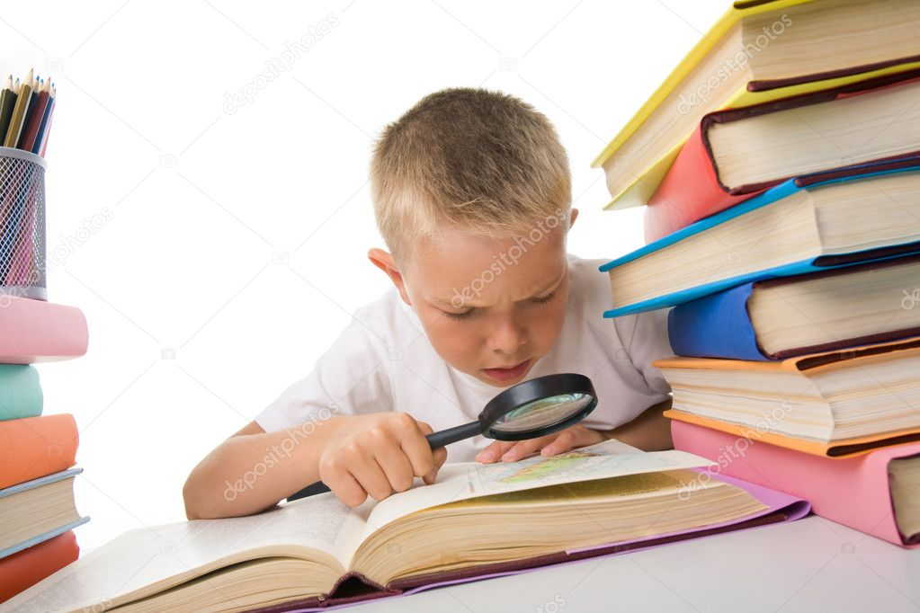 Smart youth reading open book before him with serious facial expression — Stock Photo #11127349