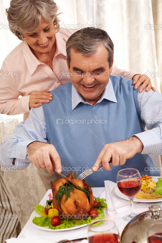 Portrait of senior man cutting roasted turkey with his happy wife behind — Stock Photo #11128272