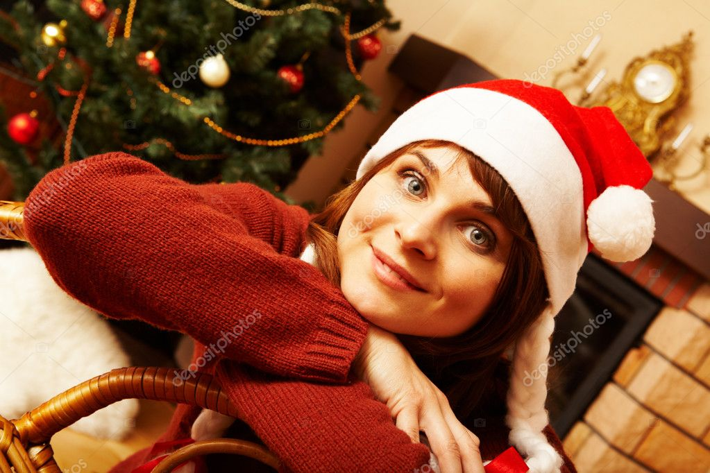 Portrait of smiling woman wearing santa cap looking at camera — Stock Photo #11128299