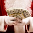 Santa hands with stacks of dollar banknotes — Stock Photo