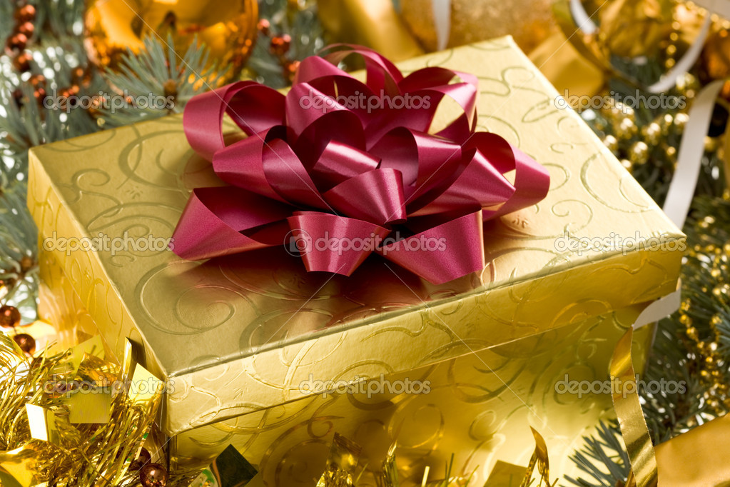 Christmas gift surrounded by golden tinsel — Stock Photo #11148001